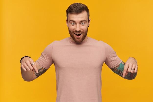 Gelukkig knappe jonge man in roze t-shirt met baard en tatoeage bij de hand kijken en naar beneden gericht met twee vingers over gele muur
