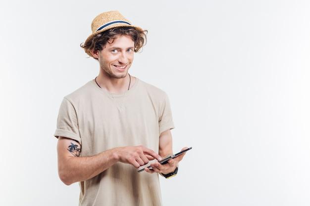 Gelukkig knappe jonge man met behulp van tablet en camera kijken op witte achtergrond