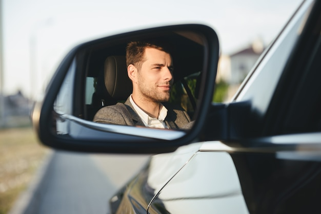 Gelukkig knappe jonge zakenman chauffeur in zijn auto