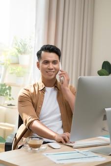 Gelukkig knappe jonge zakenman met behulp van computer en praten op mobiele telefoon in office