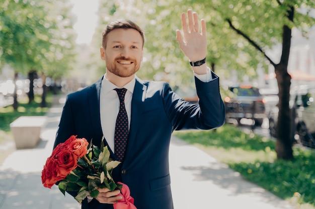 Gelukkig knappe jongeman in blauw pak met vers boeket rode rozen en hallo zwaaien, geliefde vrouw met bloemen groeten terwijl hij een romantische date in het stadspark heeft, glimlachend en geluk voelend