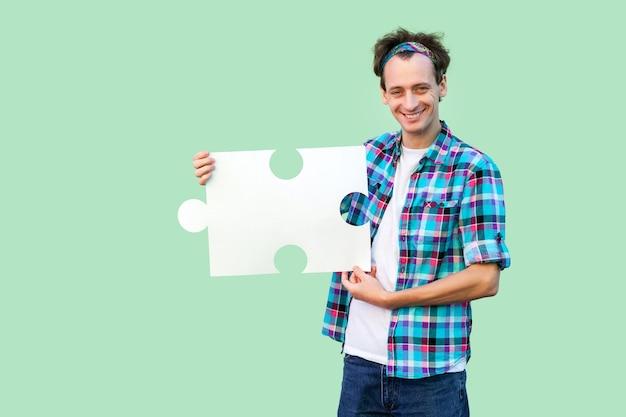 Gelukkig knappe jongeman in geruit hemd staat en houdt een groot stuk puzzel vast, kijkend naar de camera met een brede glimlach. binnen, geïsoleerd, kopieer ruimte, groene achtergrond, studio-opname