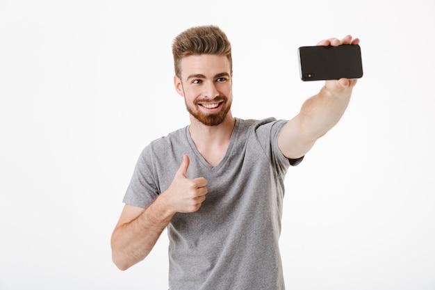 Gelukkig knappe jongeman selfie maken via mobiele telefoon met duimen omhoog gebaar.