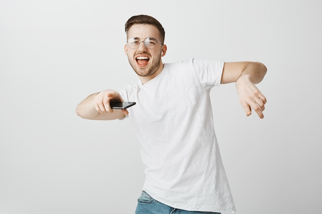 Gelukkig knappe jongen in glazen dansen op muziek in draadloze koptelefoon met mobiele telefoon in de hand