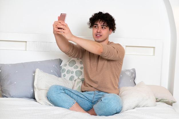 Gelukkig knappe jongen jongeman blogger zit op bed thuis in de slaapkamer en selfie foto te nemen