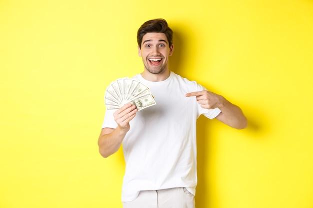 Gelukkig knappe kerel wijzende vinger naar geld, concept van krediet en lening, staande over gele achtergrond