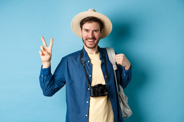 Gelukkig knappe man foto nemen op zomervakantie, vredesteken tonen en glimlachen, strooien hoed dragen en toeristische rugzak, blauwe achtergrond houden.