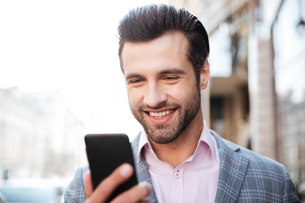 Gelukkig knappe man in jas kijken naar mobiele telefoon