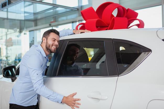 Gelukkig knappe man omarmen zijn nieuwe auto bij de dealer. opgewonden mannelijke bestuurder die giftauto met rode boog op het dak koestert