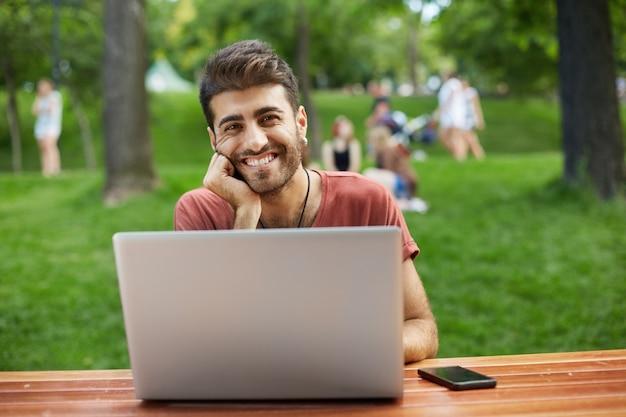 Gelukkig knappe mannelijke ontwikkelaar, freelancer kerel zitten in park met laptop en glimlachen