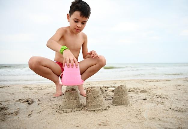 Gelukkig knappe schattige jongenskind peuter zandkastelen bouwen op het strand