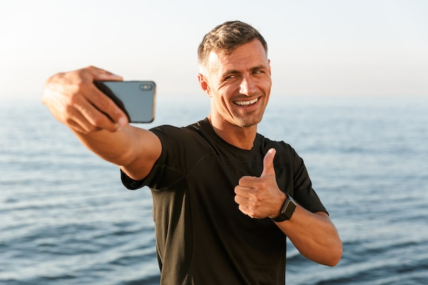 Gelukkig knappe shirtless sportman die een selfie neemt