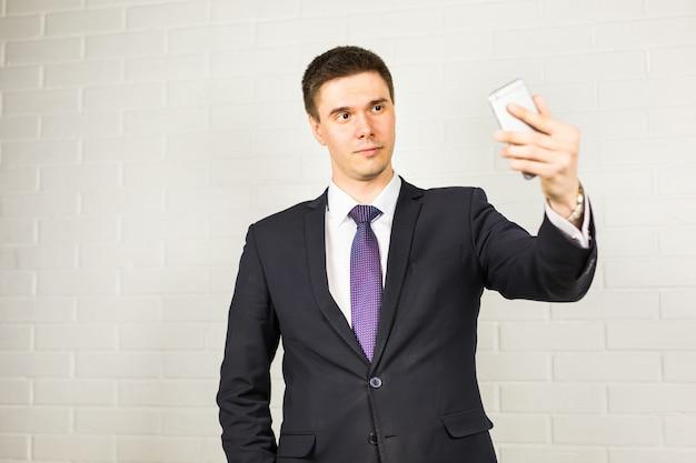 Gelukkig knappe zakenman selfie te nemen in office
