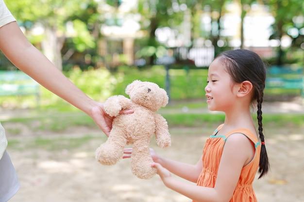 Gelukkig krijgt weinig aziatisch kindmeisje een teddybeerpop van haar moeder in het park buiten. verrassingsgeschenk van moeder voor dochter.