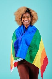 Gelukkig krullend haar vrouw die lacht terwijl ze een regenboogvlag van de lgbt-beweging op een geïsoleerde achtergrond vasthoudt.