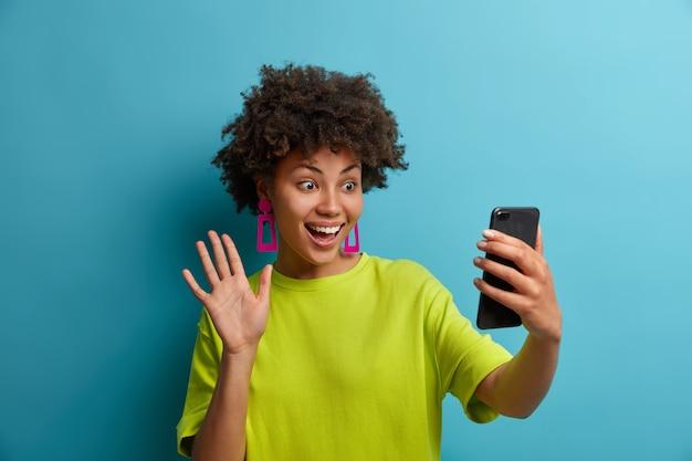 Gelukkig krullend haired duizendjarige meisje neemt selfie op smartphone, heeft een gesprek over videogesprek en golven hallo gebaar, maakt vlog-uitzending, heeft vrolijke uitdrukking, geïsoleerd over blauwe hebben