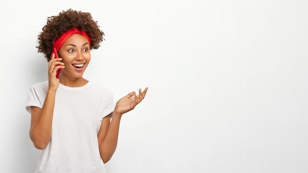 Gelukkig krullend haired meisje geniet van aangenaam telefoongesprek, gebaren met palm, mobiele telefoon gebruikt, kijkt opzij met blije uitdrukking