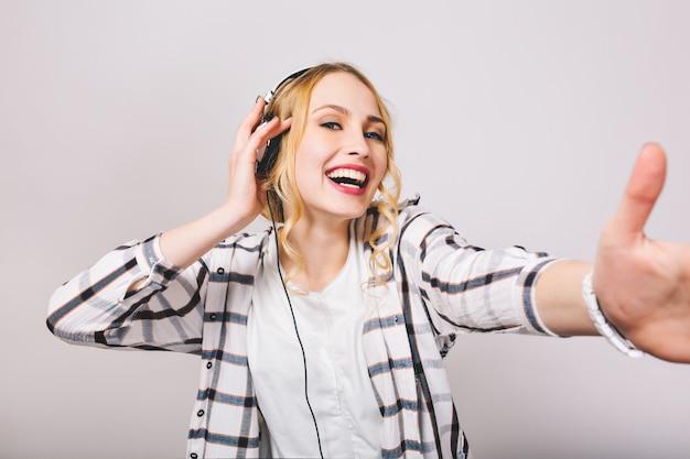 Gelukkig krullend meisje in gestreept overhemd glimlachen en dansen tijdens het luisteren naar favoriete liedje in oortelefoons. close-up portret van charmante jonge vrouw in koptelefoon met plezier