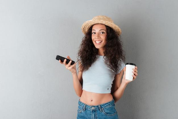 Gelukkig krullend vrouw in hoed met smartphone en koffie