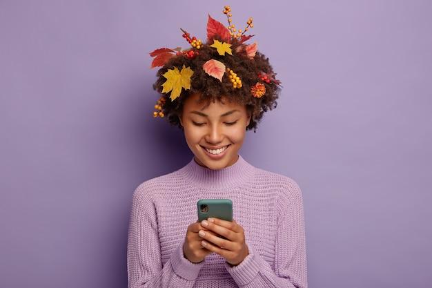 Gelukkig krullende vrouw chats met vrienden via mobiel, heeft een tedere glimlach, heeft gele bladeren op het hoofd
