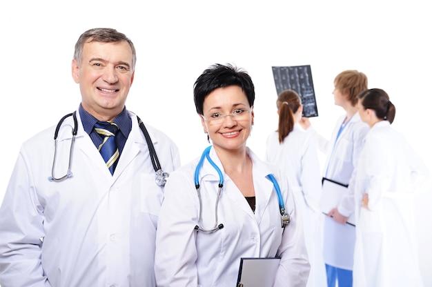 Gelukkig lachen artsen op voorgrond en drie artsen die röntgenstraling bestuderen