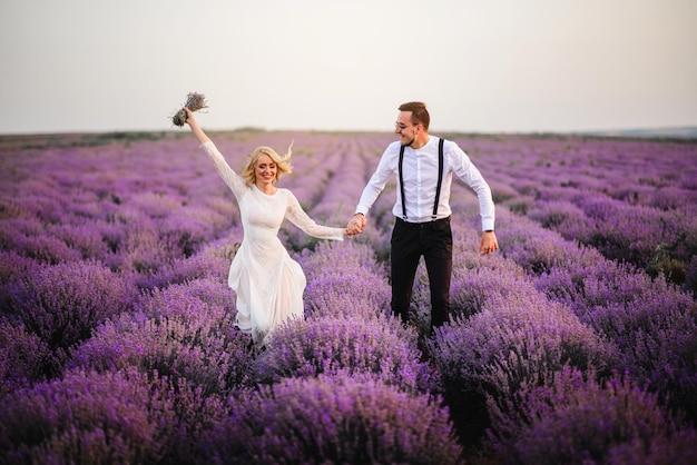 Gelukkig lachen jonggehuwden lopen op een bloeiende lavendelblauwe veld bij zonsondergang