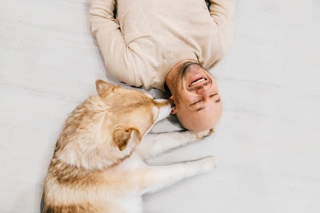 Gelukkig lachen volwassen man liggend op houten vloer met zijn mooie husky likken zijn oor