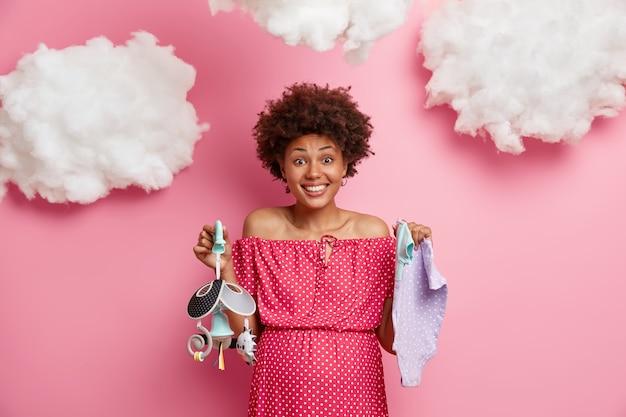 Gelukkig lachend aanstaande moeder vormt met blije uitdrukking, houdt mobiel en singlet voor baby, wacht op de geboorte van een kind, bereidt pasgeboren spullen of moedertas voor, drukt positieve emoties uit. zwangerschap