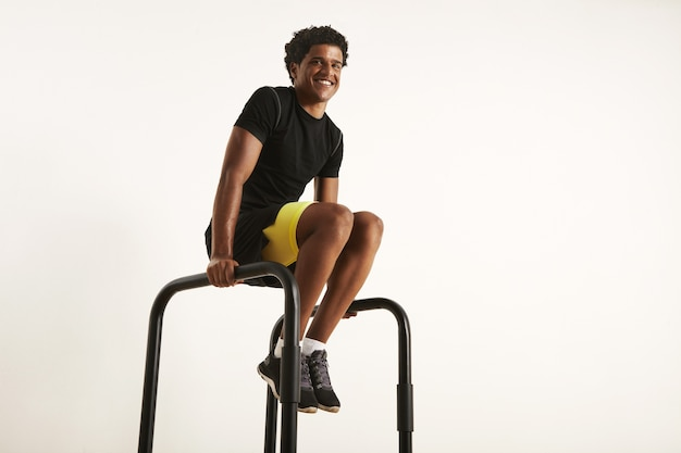 Gelukkig lachend afro-amerikaanse man in zwarte synthetische trainingstoestel thuis oefenen op parallelle staven, geïsoleerd op wit