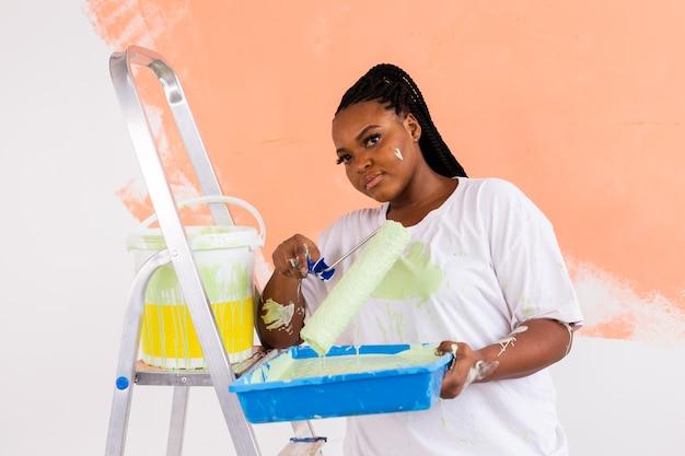 Gelukkig lachend afro-amerikaanse vrouw schilderij binnenmuur van nieuw huis. herinrichting, renovatie