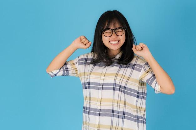 Gelukkig lachend aziatisch meisje dat zich op een blauwe achtergrond bevindt