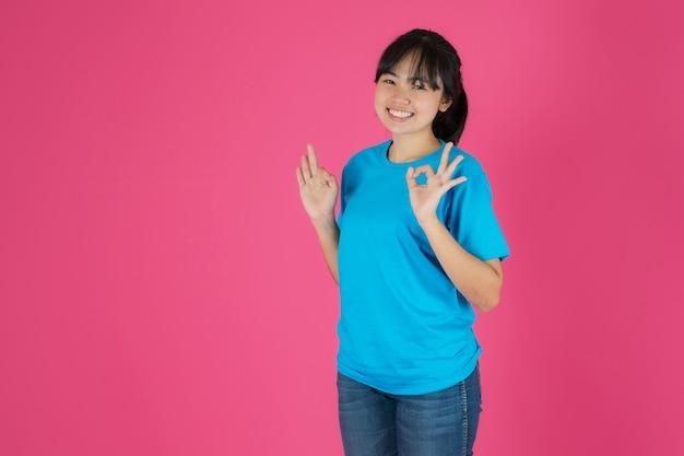Gelukkig lachend aziatisch meisje dat zich op roze achtergrond bevindt