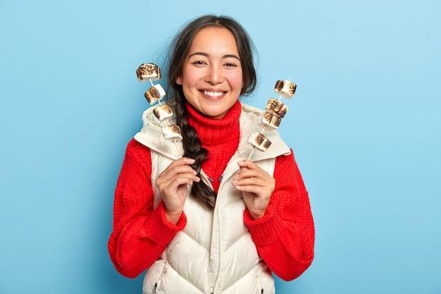 Gelukkig lachend aziatisch meisje houdt stokken met aromatische heerlijke geroosterde marshmallows, geniet van picknick op platteland, draagt warme kleren