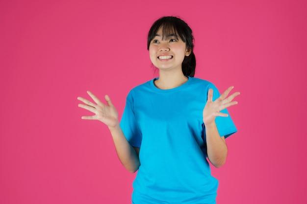 Gelukkig lachend aziatisch meisje permanent met verrassing gelaatsuitdrukking op roze achtergrond