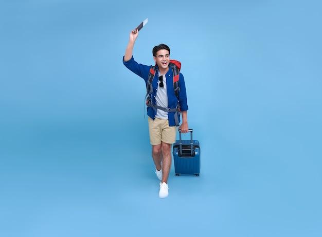 Gelukkig lachend aziatische tas packer man met paspoort en bagage genieten van hun zomervakantie uitje op blauwe achtergrond.