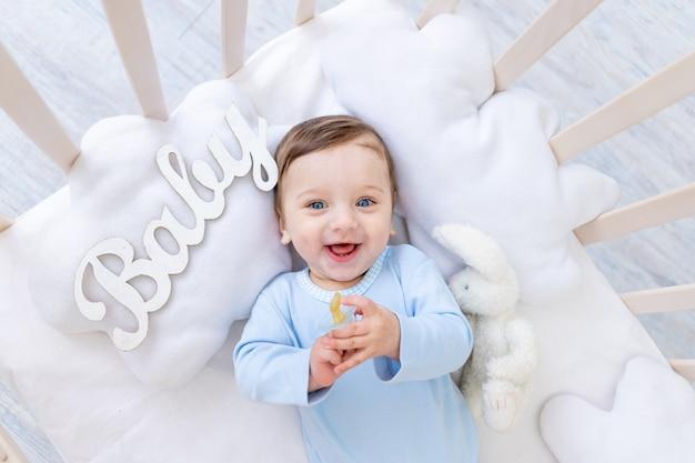 Gelukkig lachend babyjongen in de wieg met de inscriptie baby in een blauwe romper, schattige vrolijke kleine baby in de slaapkamer