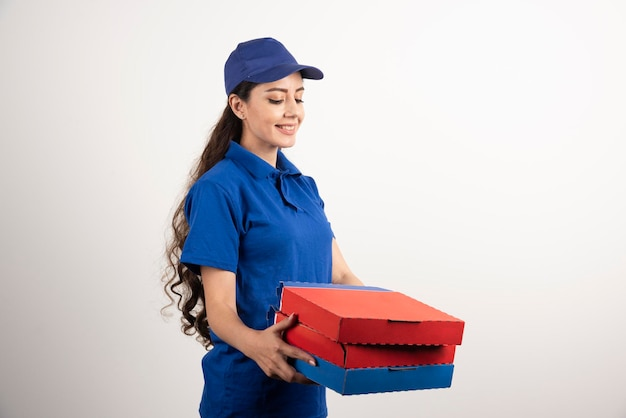 Gelukkig lachend bezorgmeisje in blauw uniform met afhaalpizzadozen op witte achtergrond. hoge kwaliteit foto