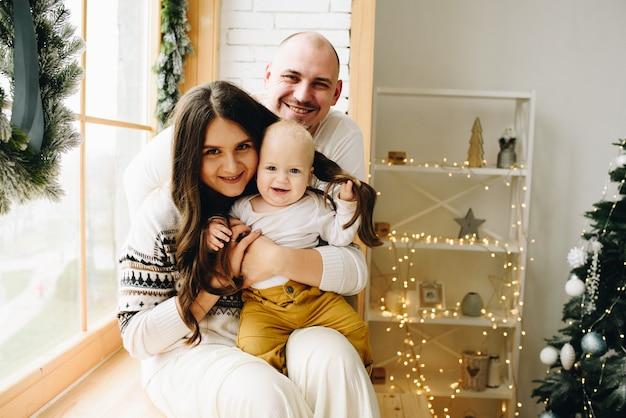 Gelukkig lachend blanke gezin van drie in fraai ingerichte kamer