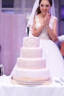 Gelukkig lachend bruid permanent door mooie hoge bruidstaart indoor in restaurant. witte feestelijke taart versierd met een mastiek op tafel.