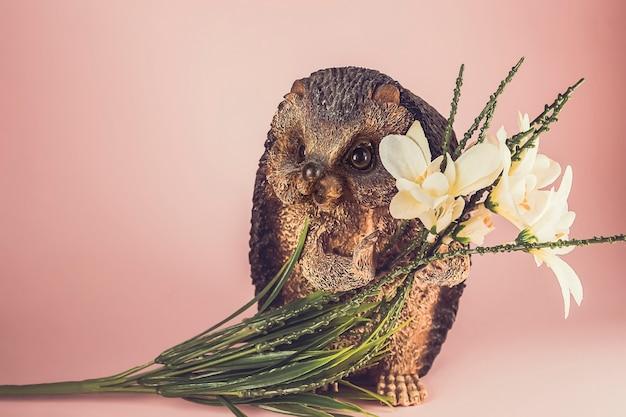 Gelukkig lachend decoratieve keramische beeldjes egel met bloemen op een roze achtergrond.