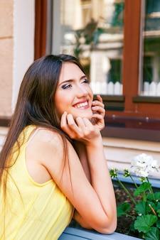 Gelukkig lachend dromend meisje poseren in de buurt van venster, lang donkerbruin steil haar en natuurlijke make-up, mooie zonnige zomerdag.
