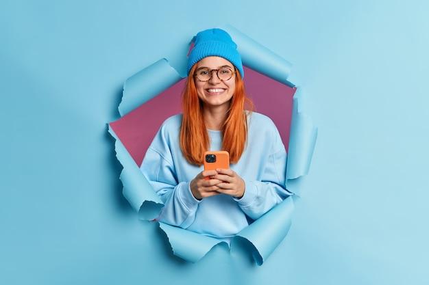 Gelukkig lachend duizendjarige meisje met rood haar houdt moderne cellulaire geniet van sms'en op sociale media maakt gebruik van mobiele netwerkdiensten draagt blauwe trui en hoed.