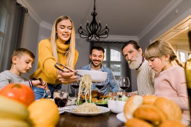 Gelukkig lachend familie, grootvader, ouders en kinderen aan feestelijke tafel zitten en lekker eten