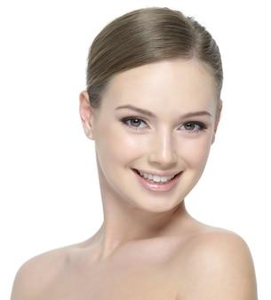 Gelukkig lachend gezicht van jong mooi tienermeisje met schone huid op wit wordt geïsoleerd
