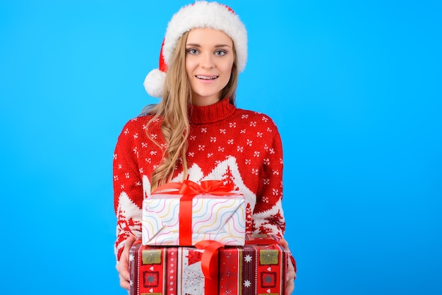 Gelukkig lachend heerlijke mooie jonge vrouw in kerstmuts gebreide trui houdt een stapel cadeautjes, geïsoleerd op blauwe achtergrond
