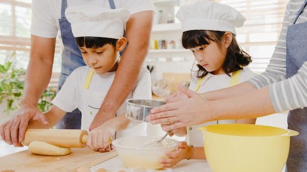 Gelukkig lachend jong aziatisch japans gezin met kleuters, veel plezier met het bakken van gebak