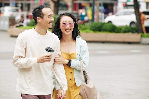 Gelukkig lachend jong chinees stel met koffie die buiten loopt op een winderige dag