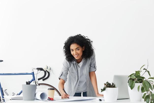 Gelukkig lachend jong gemengd ras geschoolde vrouwelijke ingenieur met afro kapsel