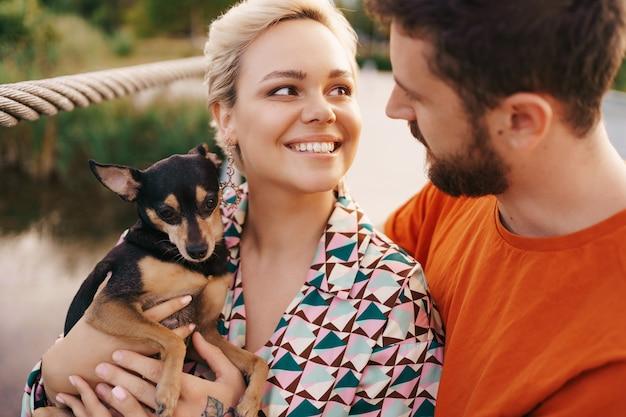 Gelukkig lachend jong koppel knuffelen hun hond op brug