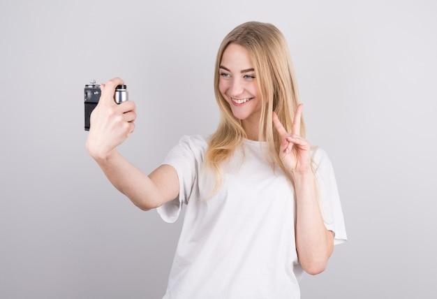 Gelukkig lachend jong meisje camera houden en fotograferen van zichzelf